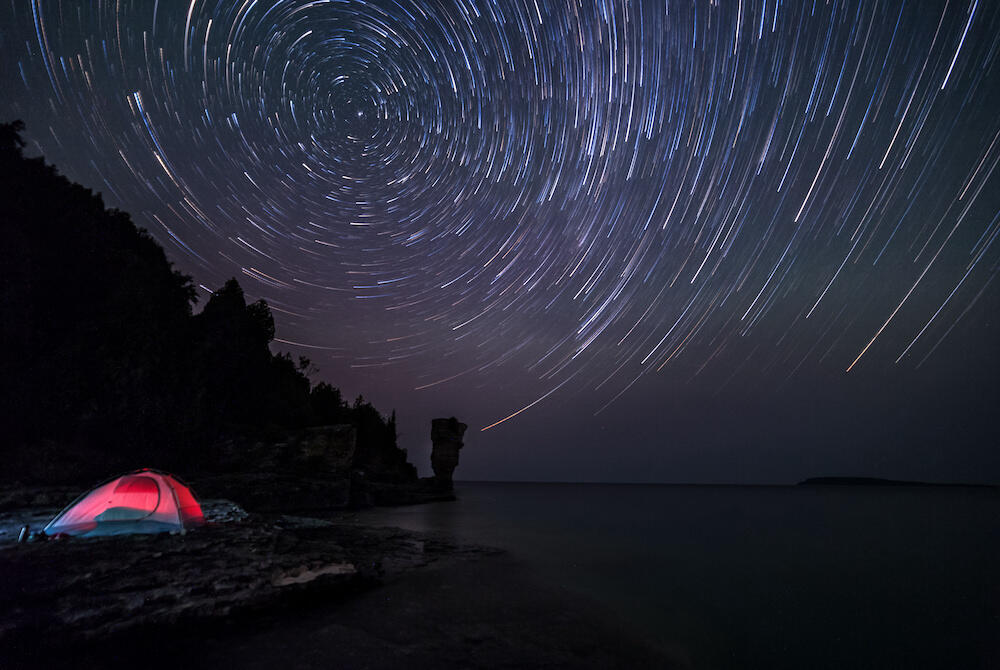 Stars overhead with tent lit up beside water