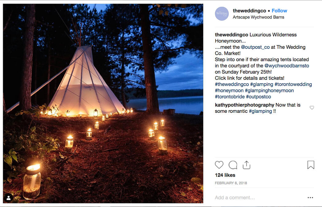 Lakeside teepee at night with candles lighting a path