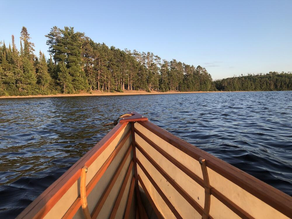 Bow of canoe pointing at beach with pines on it