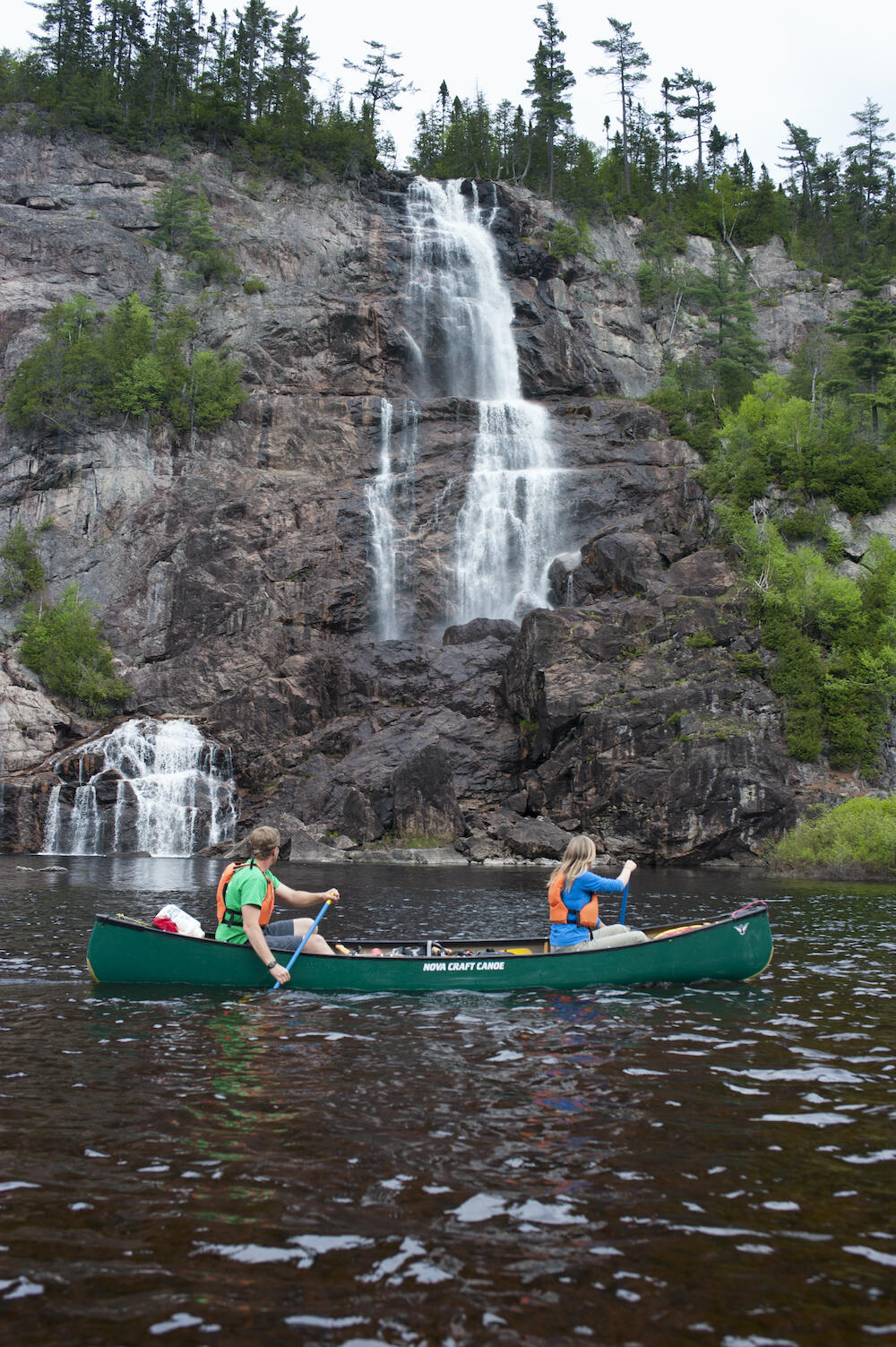 People canoeing beside a waterfall