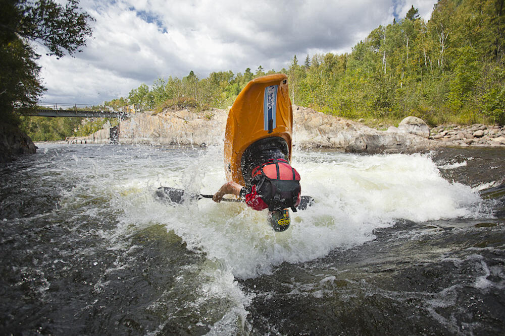 Person in whitewater kayak doing a flip