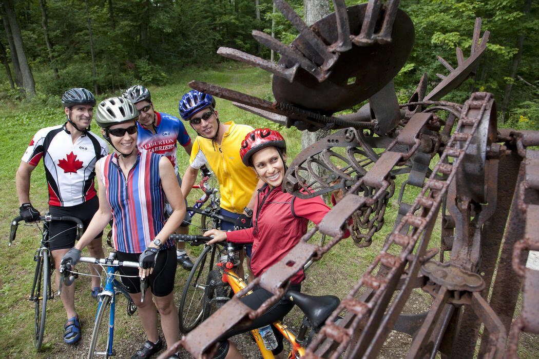 Group of cyclists looking at an art display.