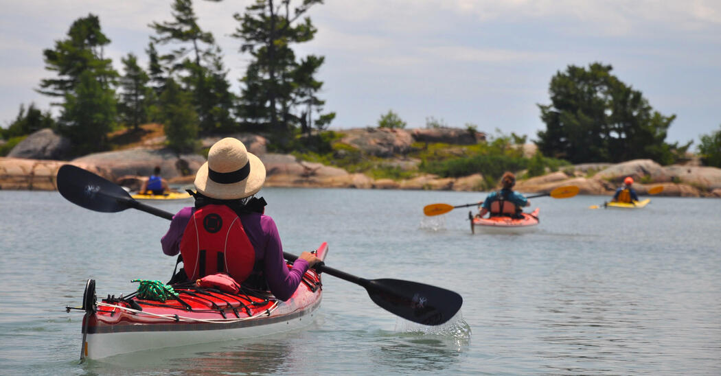 Woman paddling in kayak among sheltered smooth rock islands