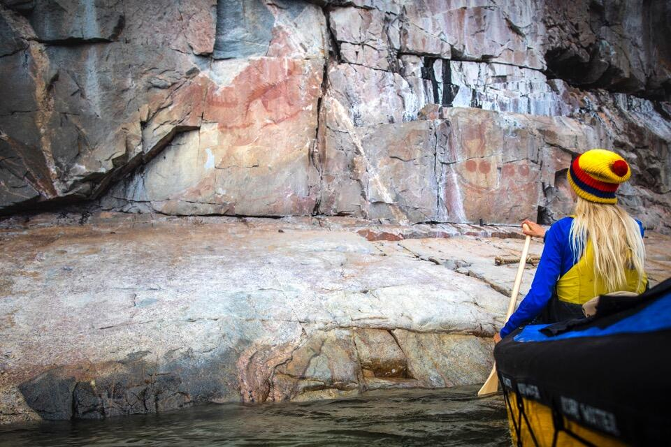 Woman in bow of canoe looking at pictographs.
