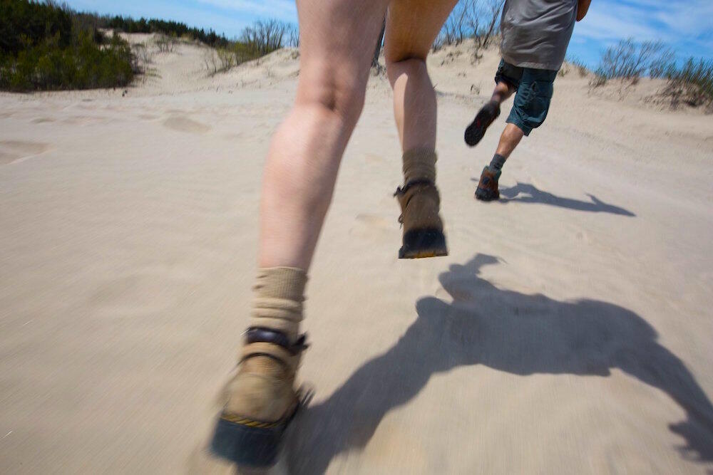 Two people in hiking boots running on sand.