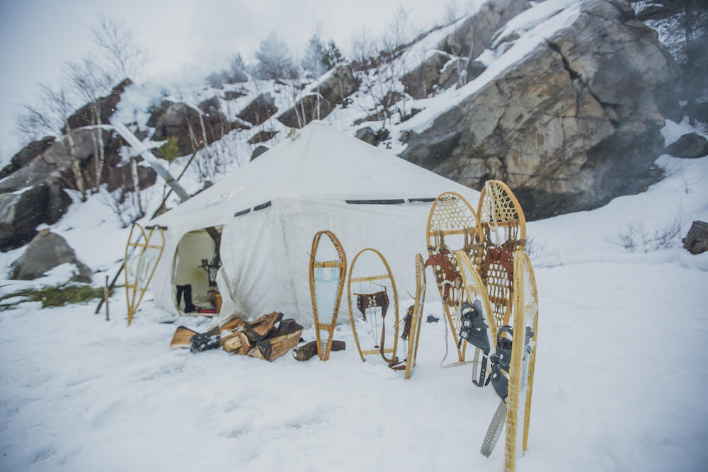 Traditional heated wall canvas tent in snow with snowshoes.
