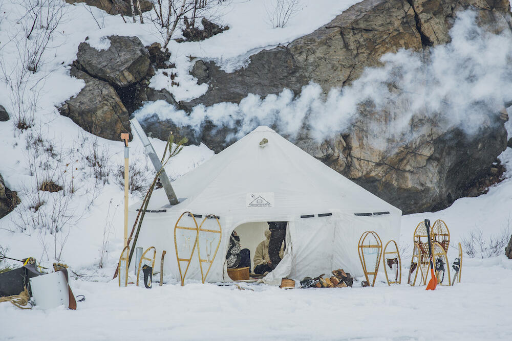 Large white canvas tent with smoke coming out of a stove pipe, surrounded by snow.