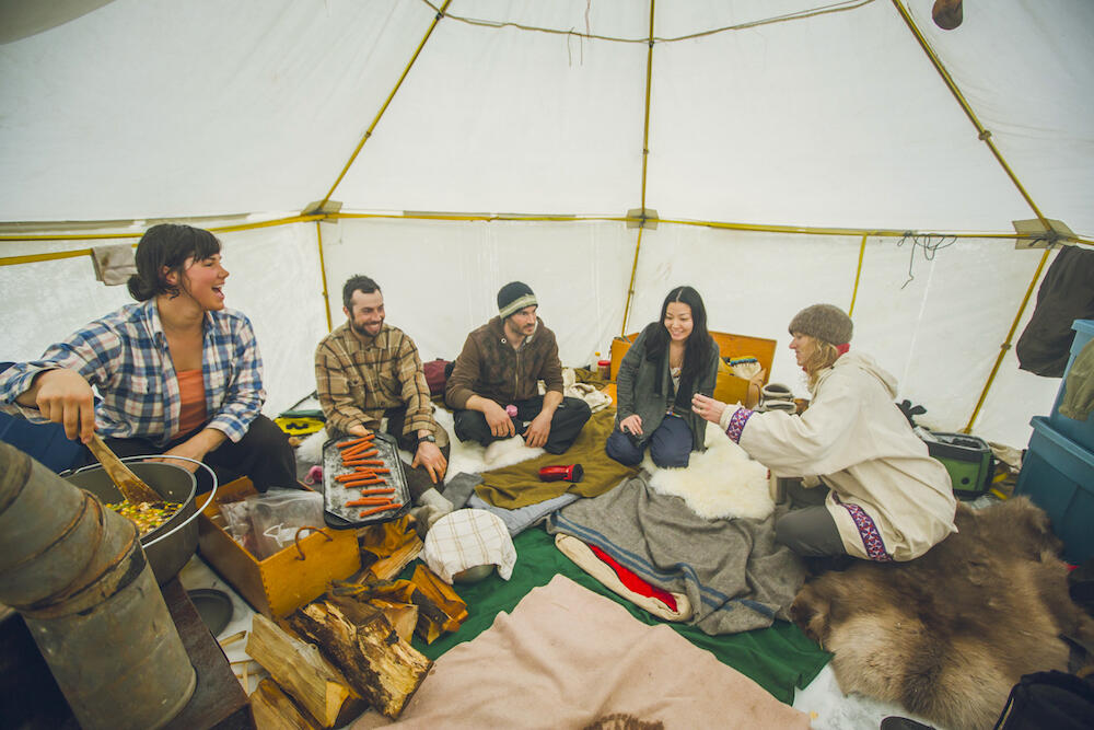 Group of happy people inside a heated canvas tent