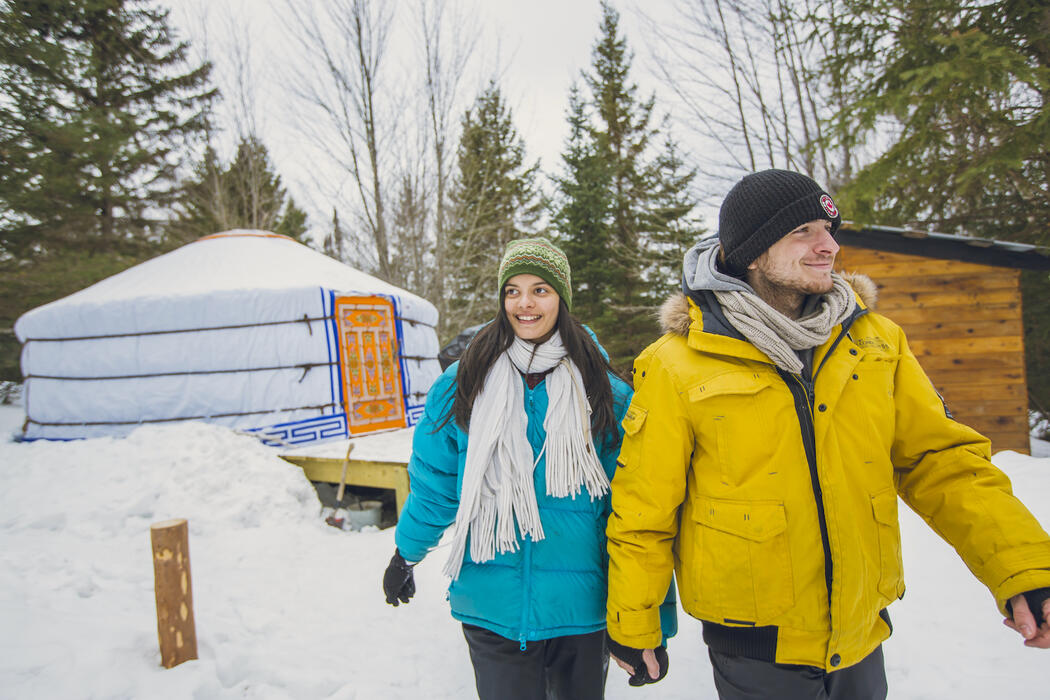 A couple walking in front of a Mongolian yurt in the winter.