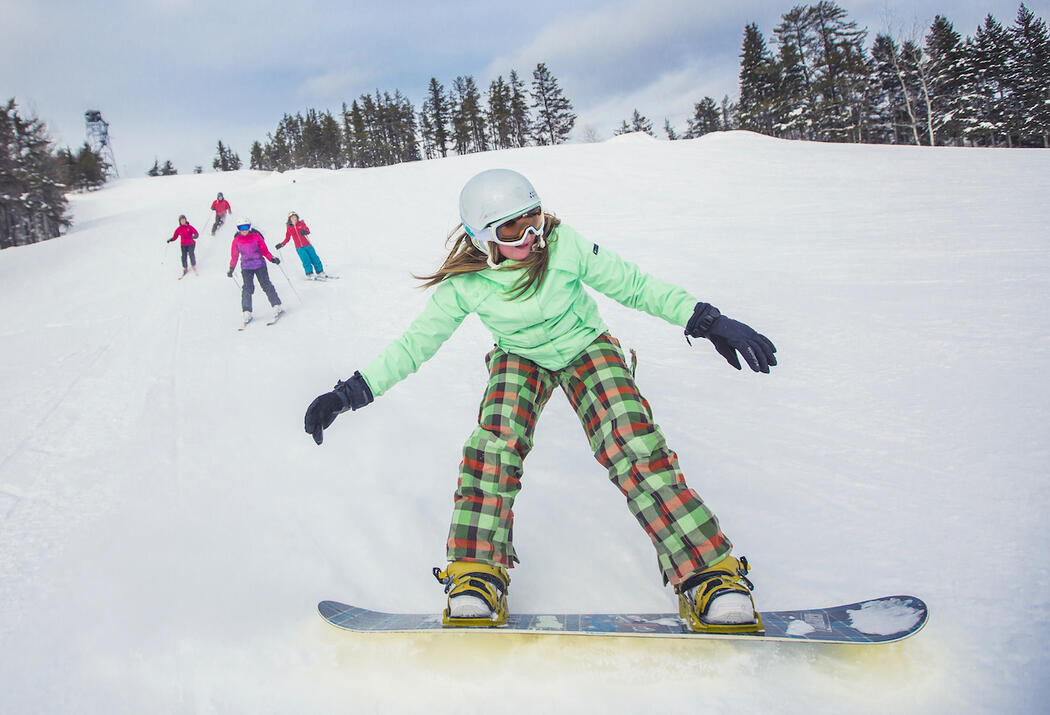 Girl on snowboard with 4 skiers on slope in background