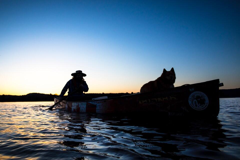 Silhouette of a man paddling a canoe with a dog in front of canoe.