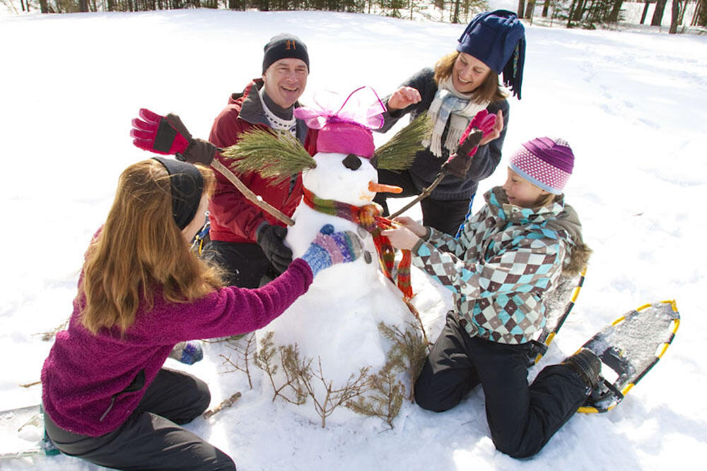 Group of people building a snowman.