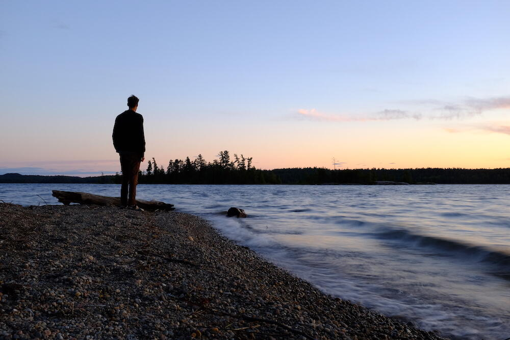 Man standing on edge of a lake at sunset
