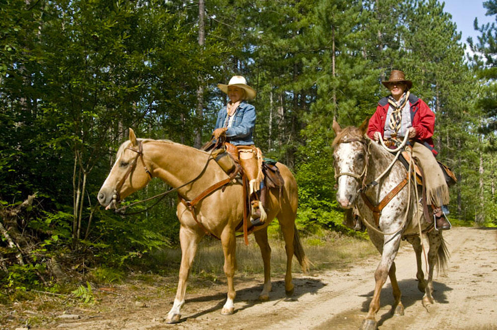 Two women riding horses on a trail in the forest.