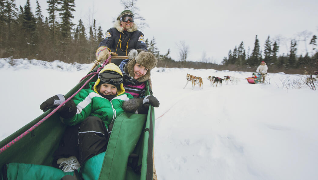 Woman and child in dogsled basket with man driving.