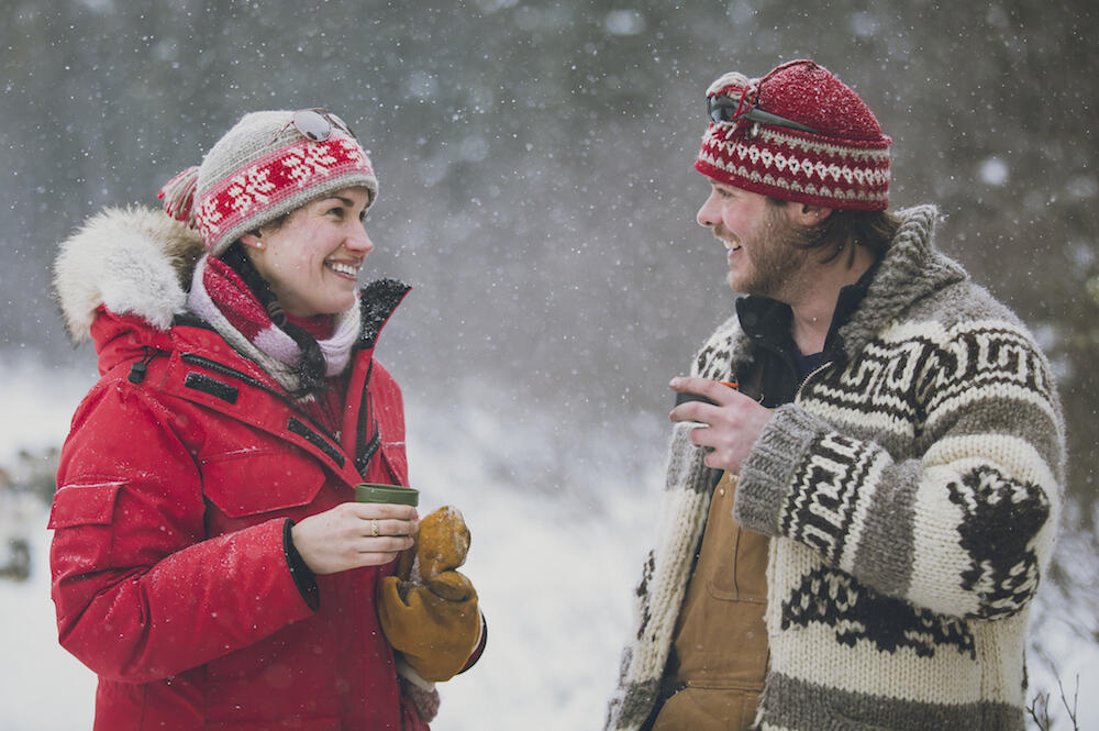 A man and a woman in winter clothing drinking a cup of hot chocolate