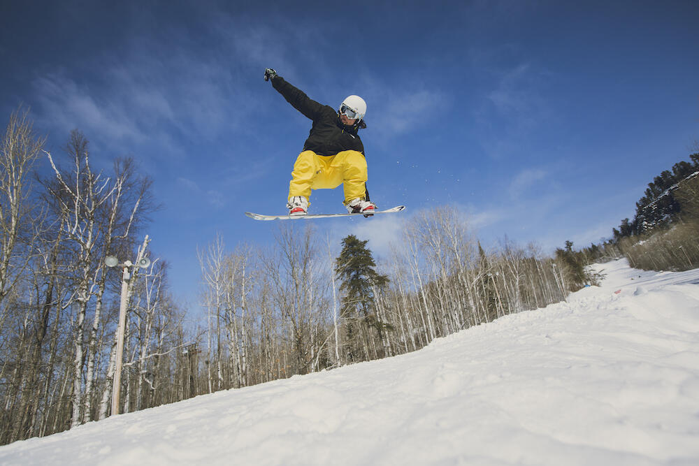 Young man catching air on a snowboard
