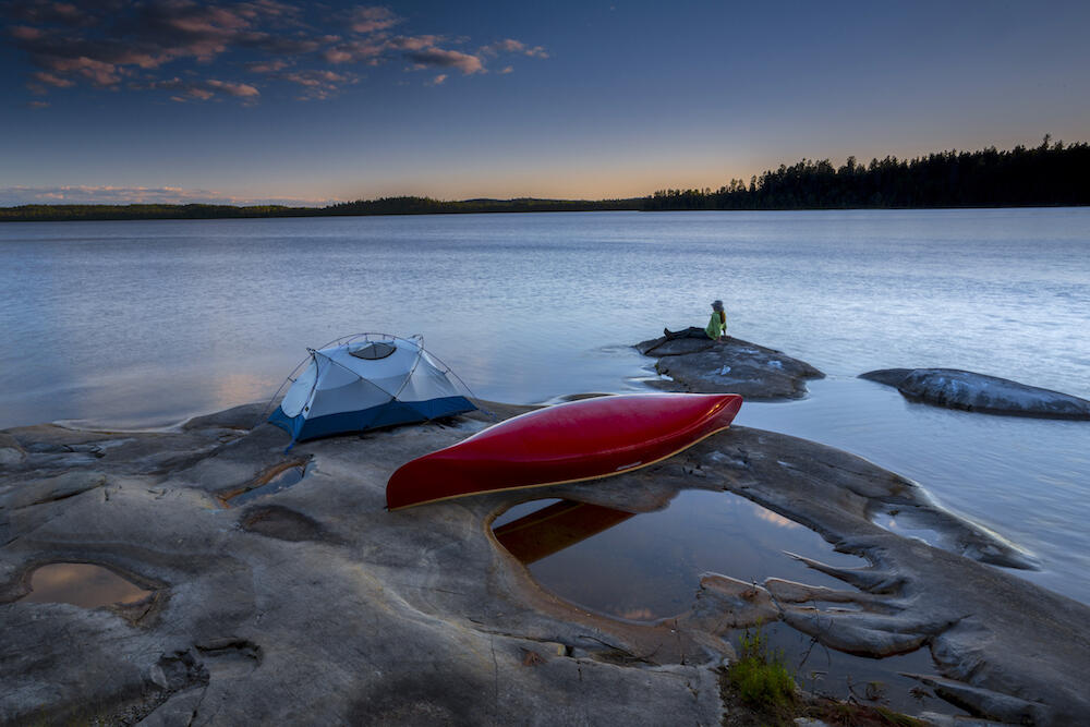 Tent and canoe on smooth rock by lakes edge at sunset