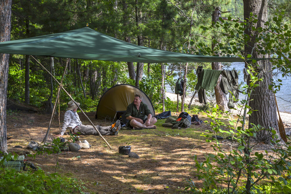 Two men sitting in forest campsite