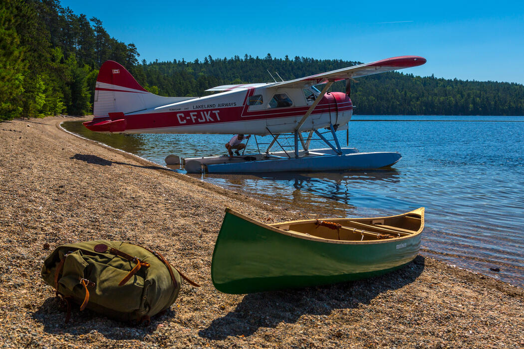 Float plane parked on beach shore beside a green canoe