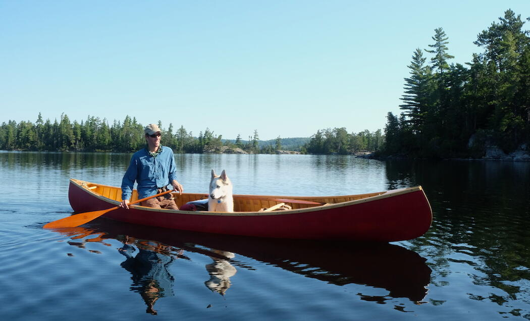 Man paddling a red canoe with a dog sitting in it.