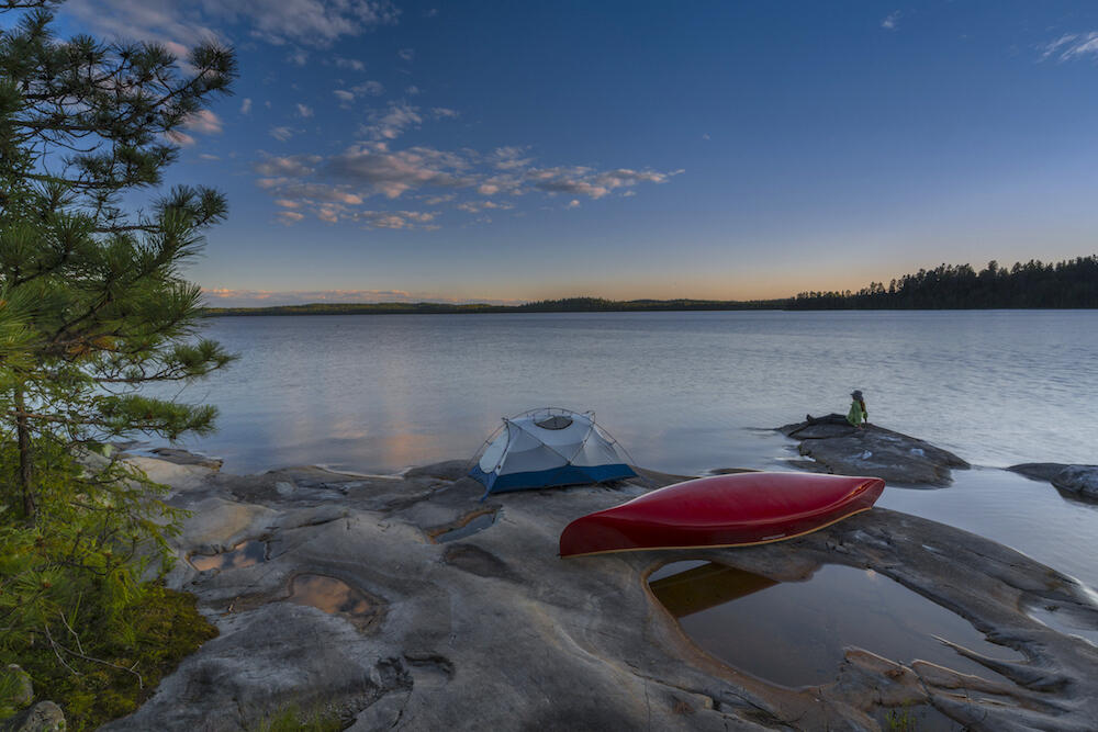 Tent and canoe on smooth rocky point at sunset.