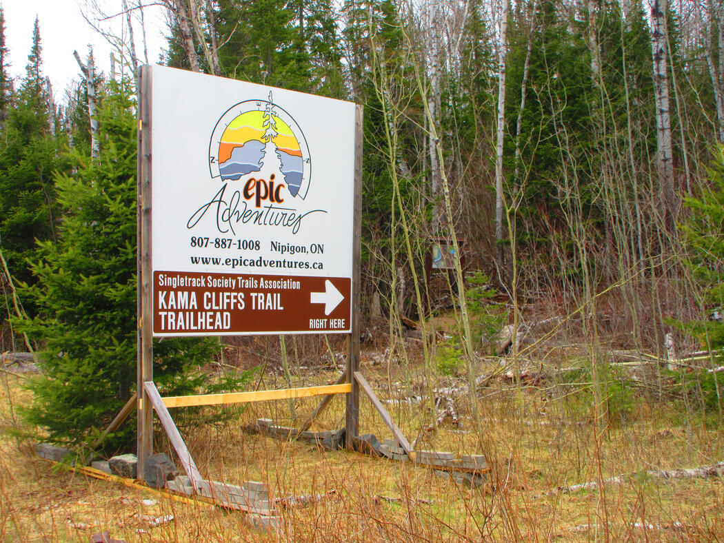A large sign at the side of Highway 17 directs hikers to the trail head of Kama Cliffs Trail.