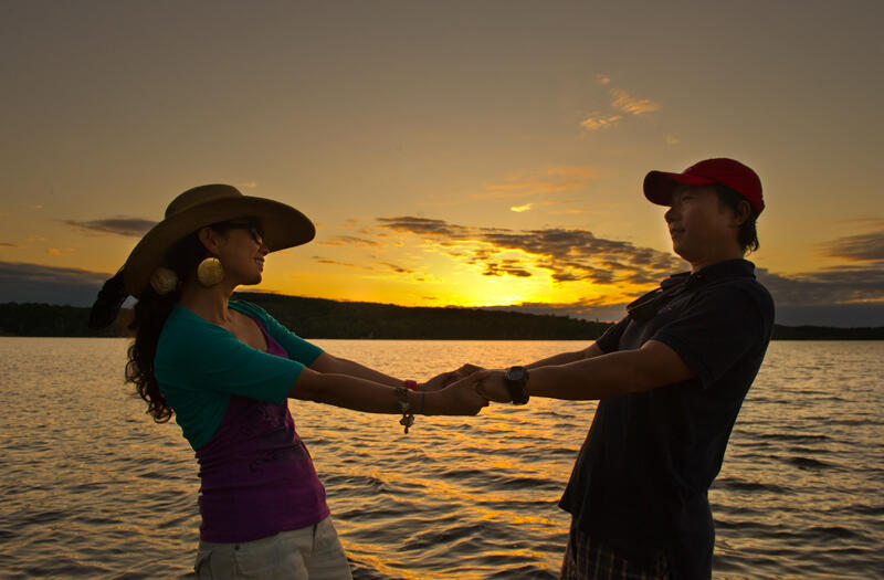 Couple holding hands beside a lake at sunset.
