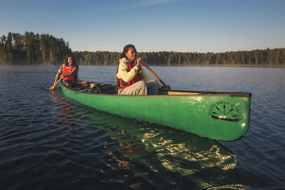 Man and woman paddling a green canoe
