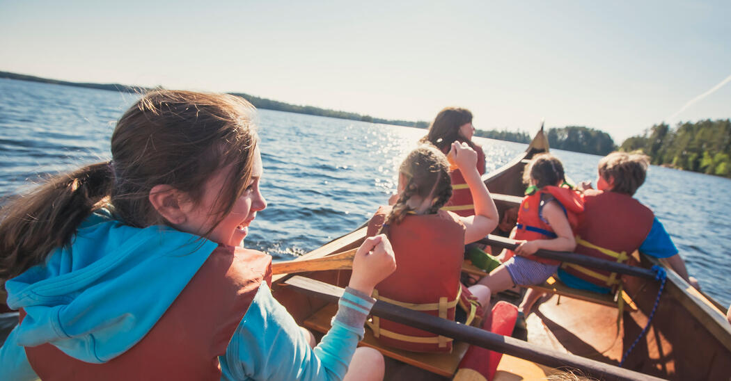 Children smiling while paddling in a voyageur canoe.