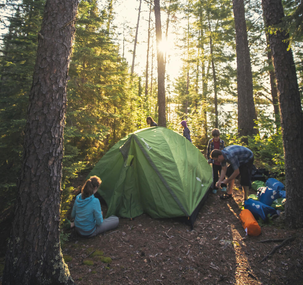 Family setting up a tent in the forest