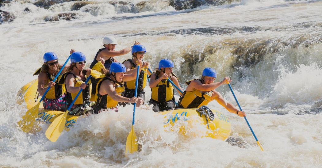 Seven people with paddles in a yellow raft in whitewater