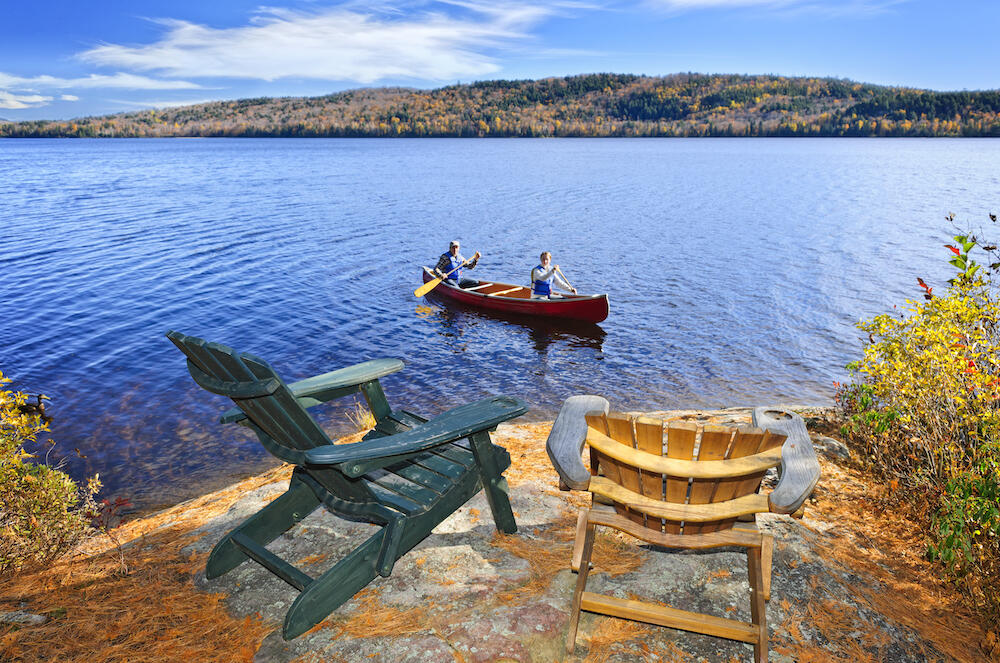 Muskoka chairs on a rock with people in canoe paddling by.