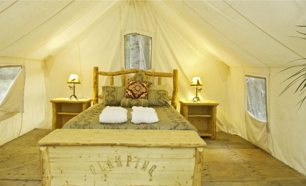 Inside of a prospector tent with wooden bed and nice bedding