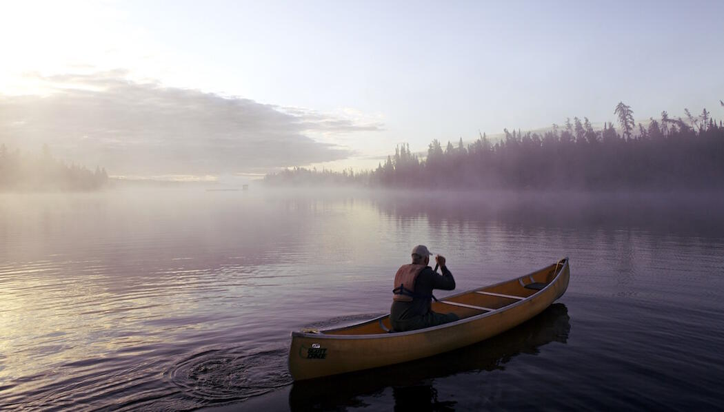Single man paddling a canoe in early morning mist.