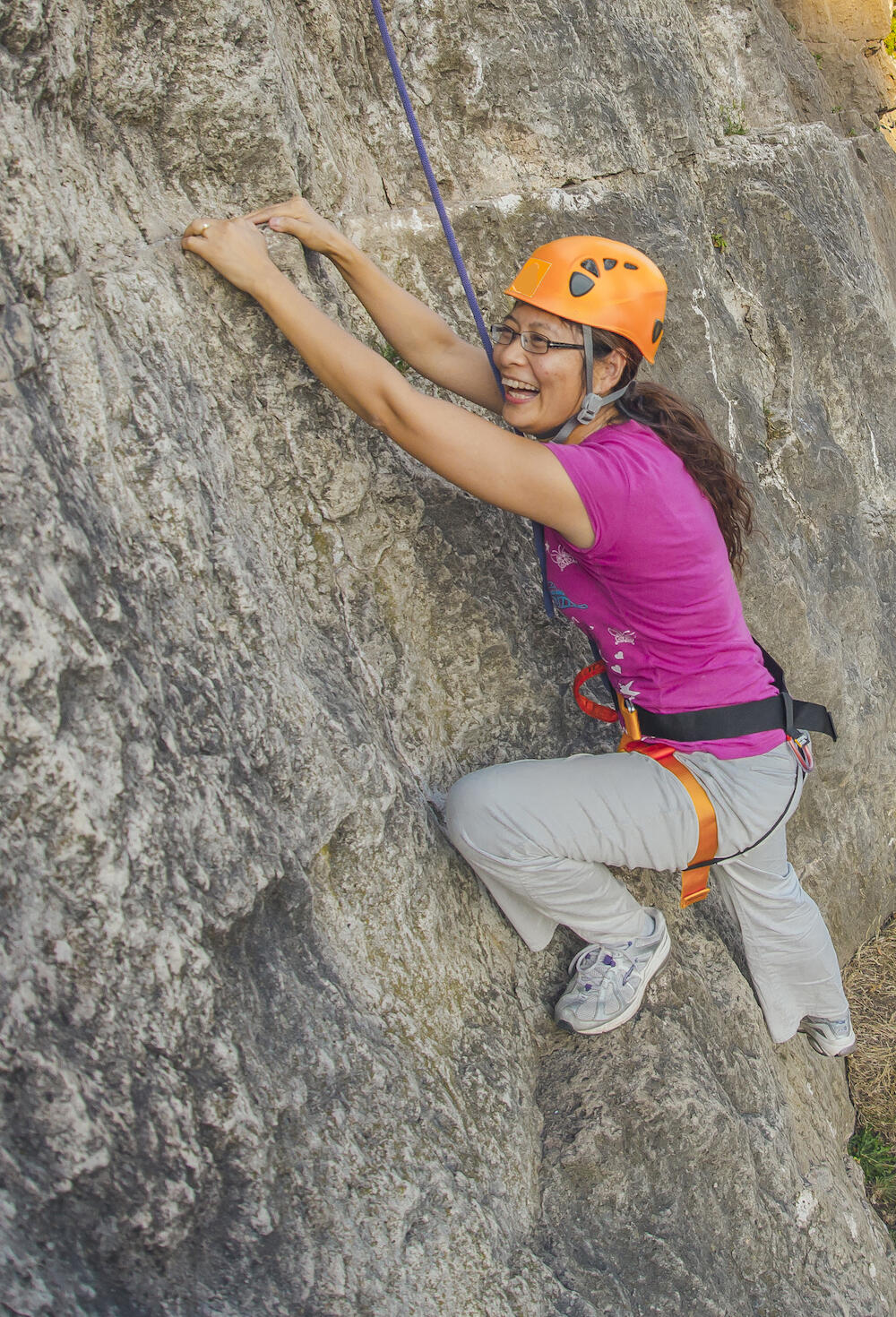Woman with big smile rock climbing