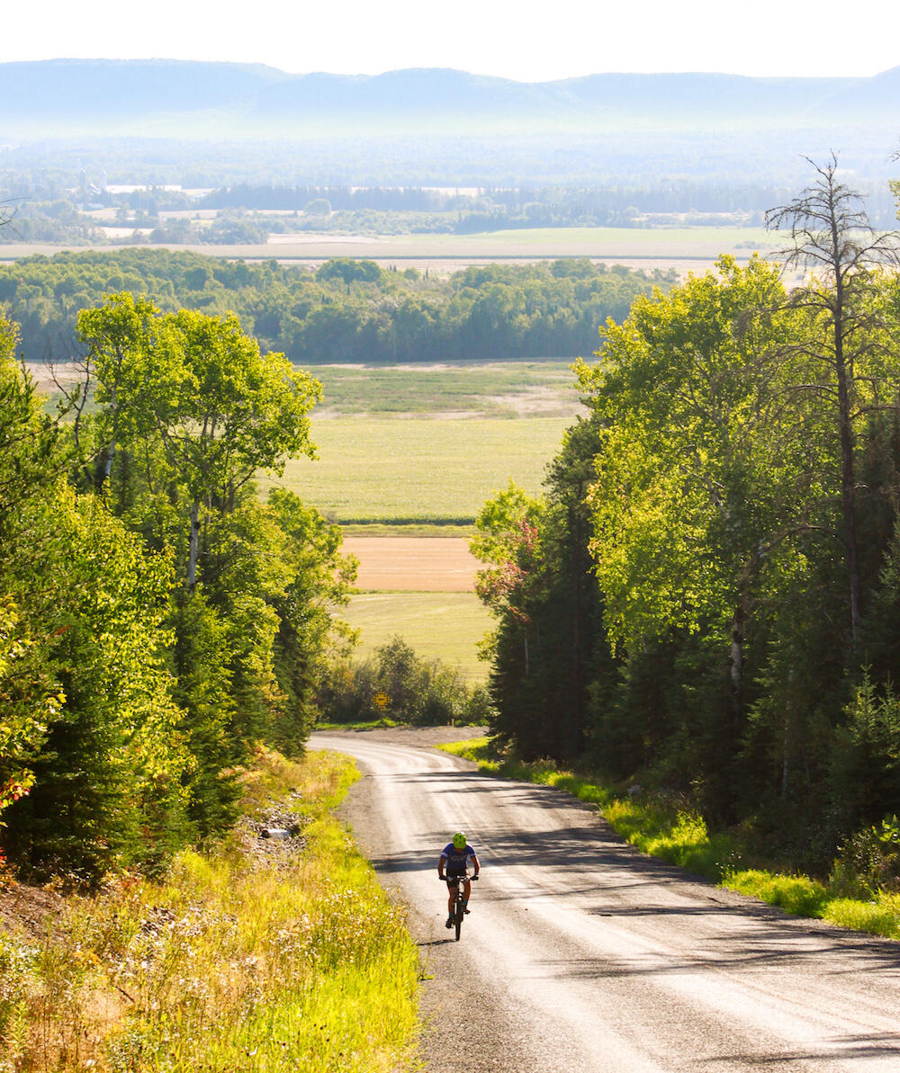 Single cyclist pedalling uphill on a dirt road with rolling hills in background.