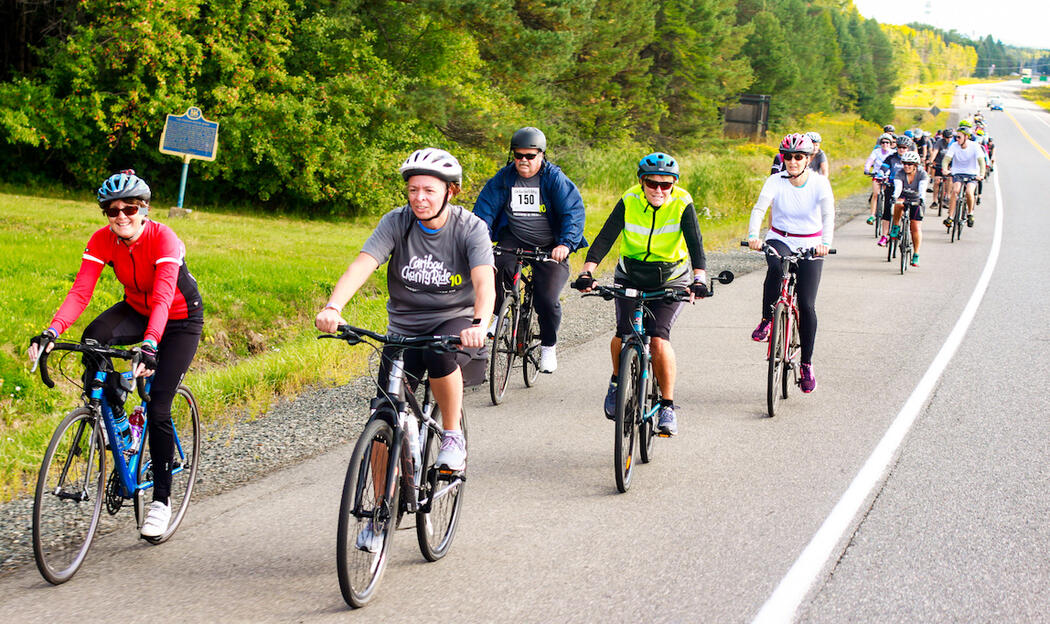 Large group of cyclists riding on paved shoulder of road