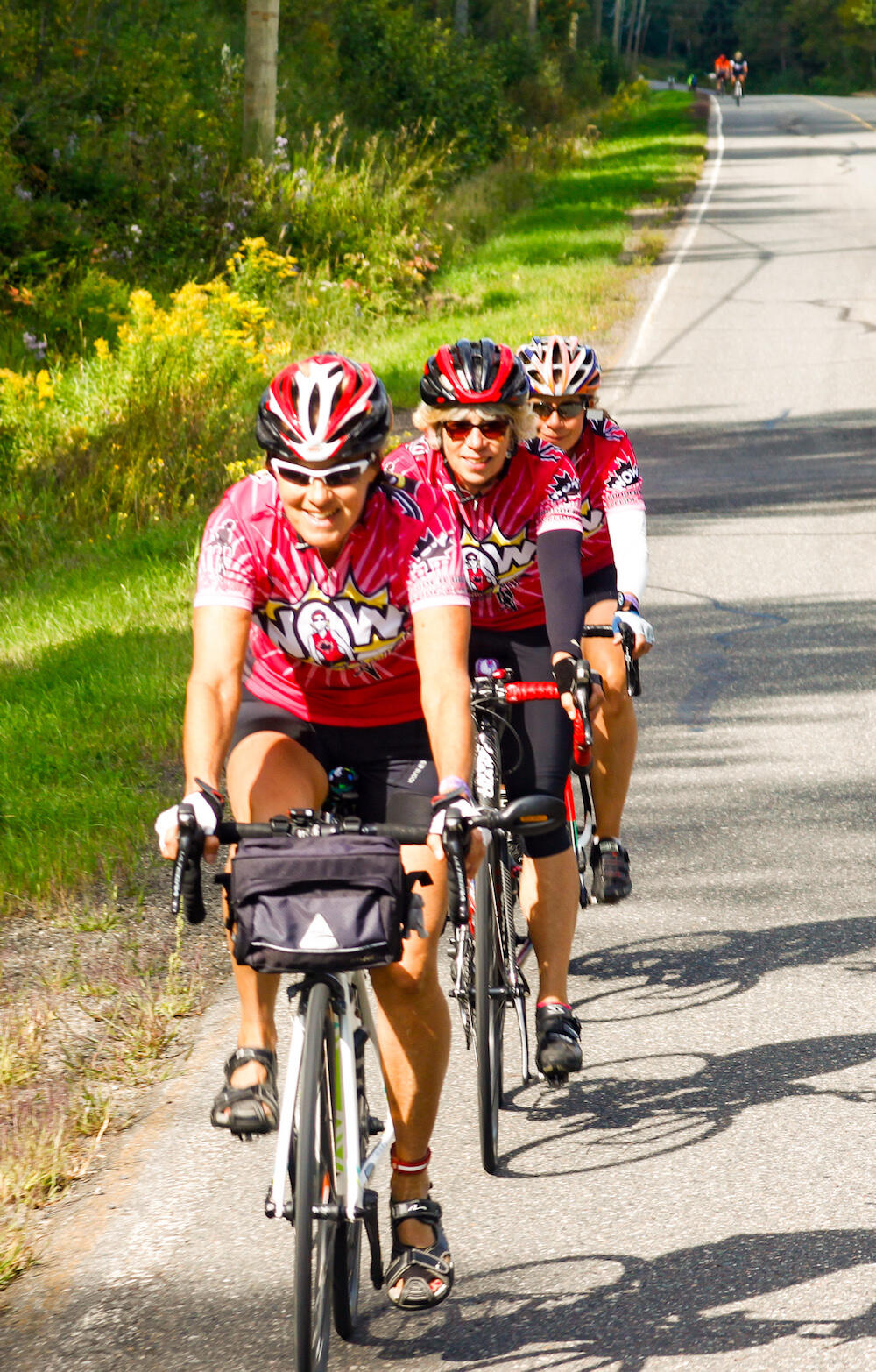Three women cyclists dressed in colourful spandex riding in single file on road