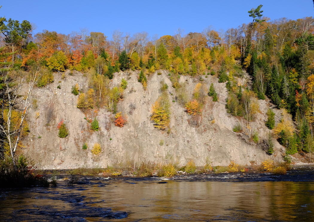River meanders in front of a steep rock wall