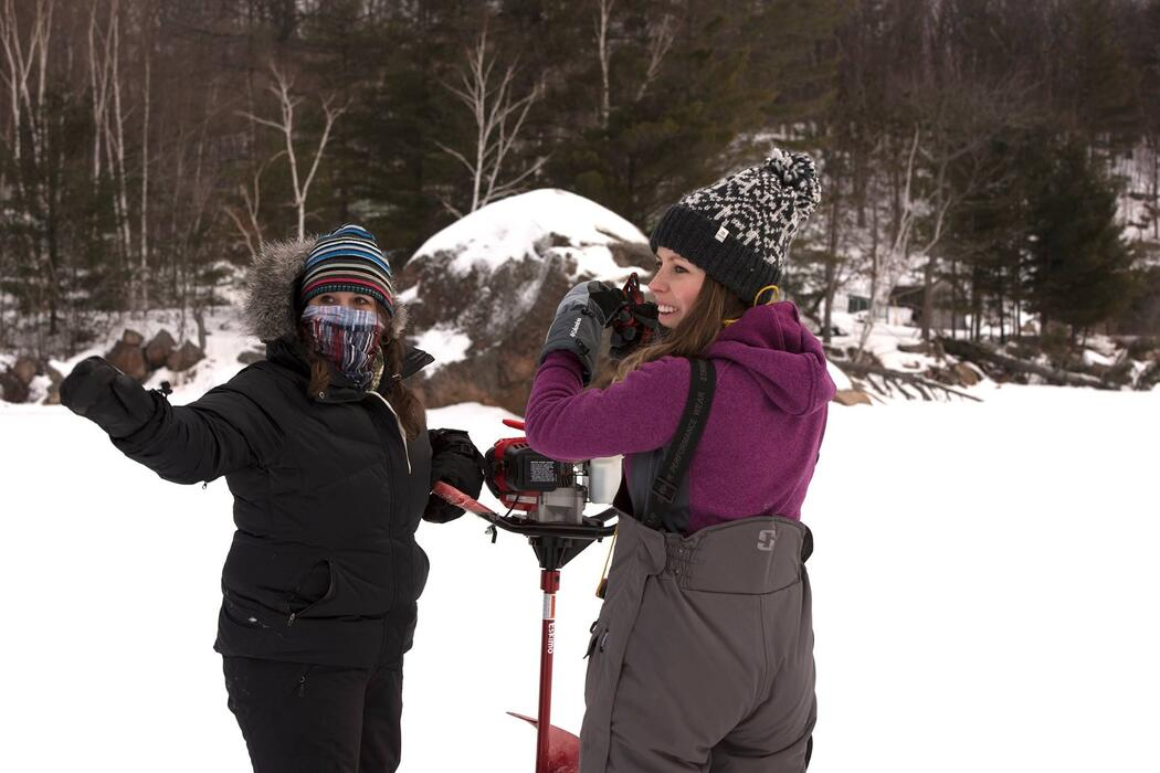 woman anglers drilling ice hole with auger