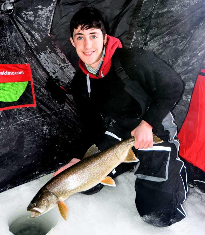 young ice angler holding lake trout
