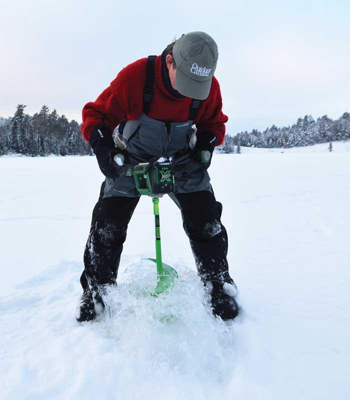 ice angler drilling hole in ice