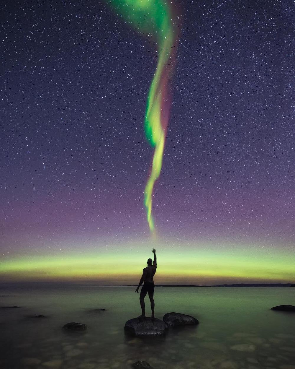Person standing on a rock near lake shore and reaching up to touch Northern Lights in sky