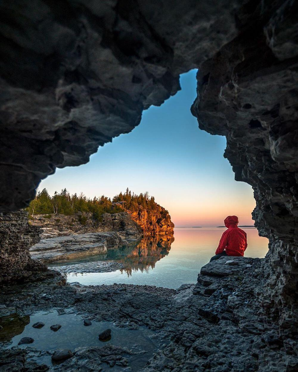 Person sitting in cave next to a lake
