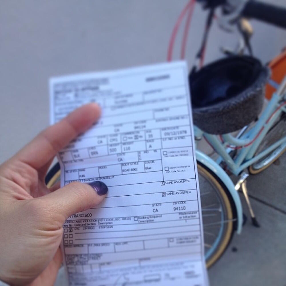 Woman holding a ticket in front of a bike