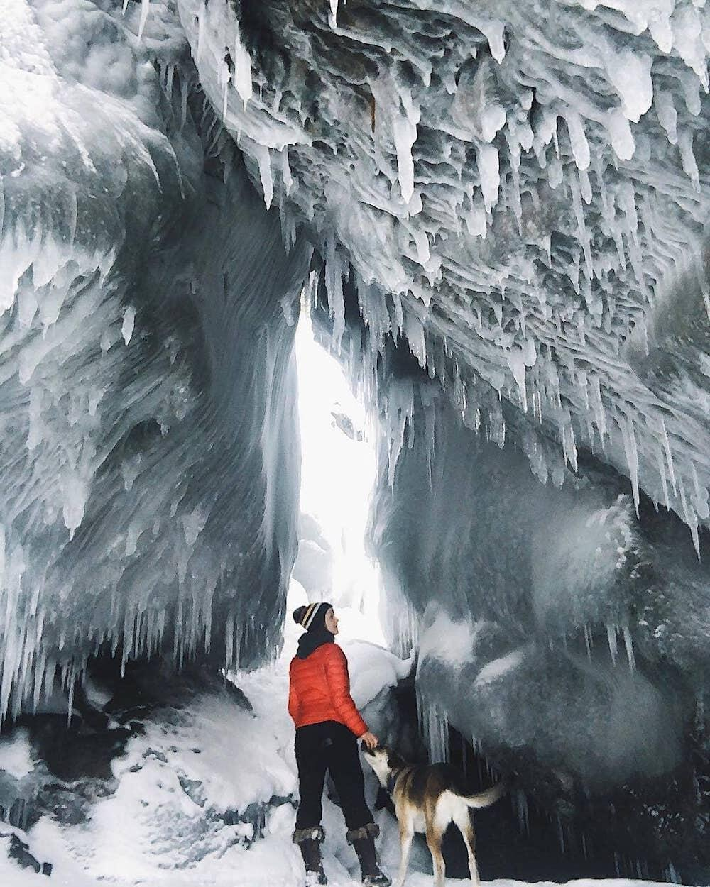 Woman and dog staving in ice cave