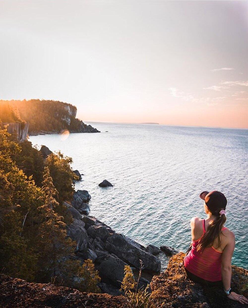 Woman sitting on cliff overlooking the water.