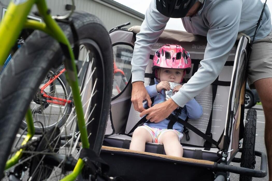 Young child being strapped into a bicycle trailer.