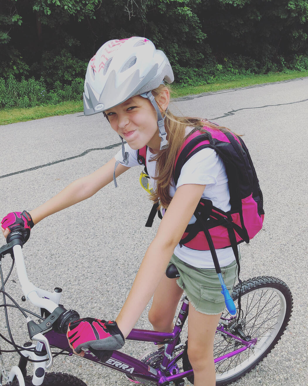 A girl, smiling, wearing a bicycle helmet and sitting on a bike.